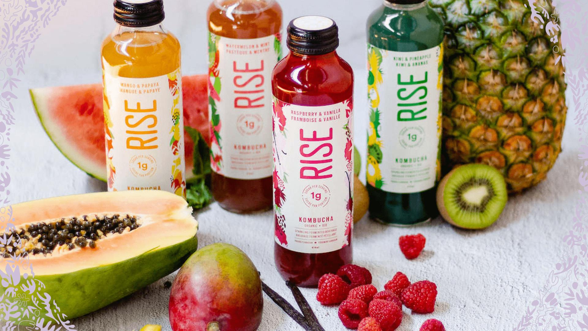 RISE kombucha bottles surrounded by various fruits