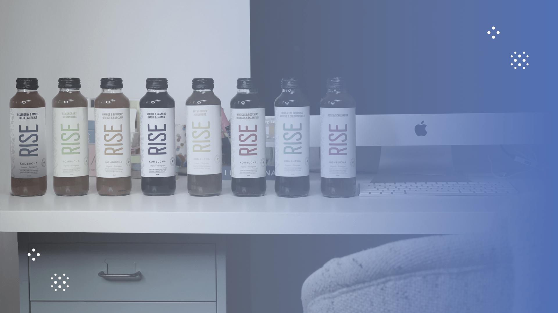 RISE kombucha bottles lined up on desk